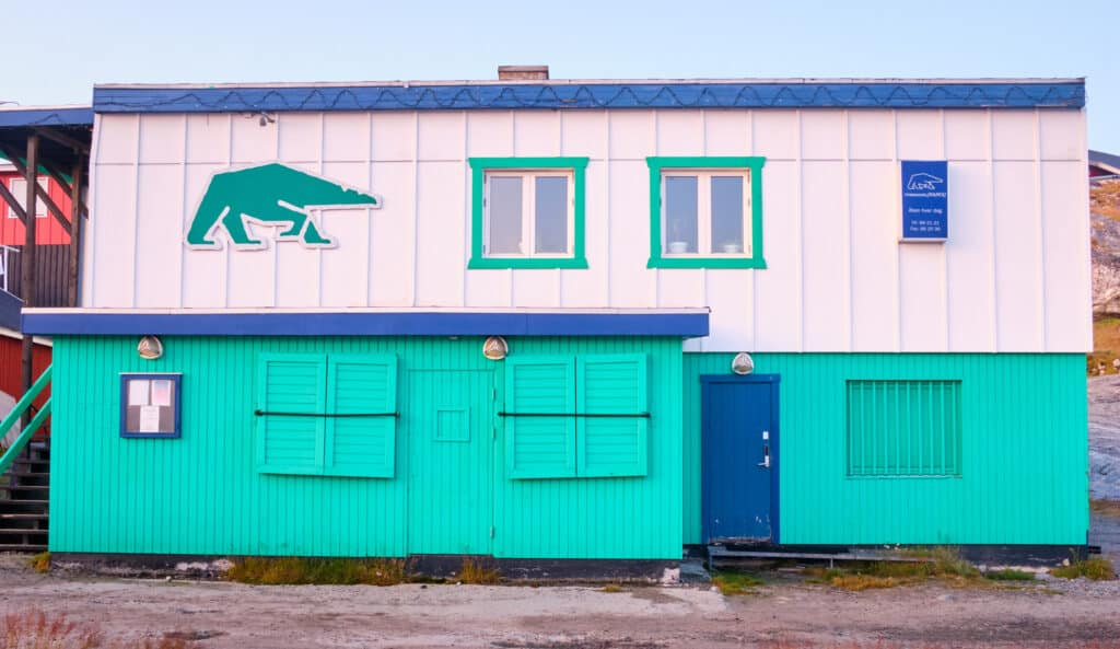 Restaurant Nanoq, Nanuaraq bar, and the disco are all contained within this green, blue, and white building