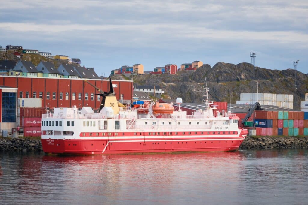 The red Sarfaq Ittuk passenger ferry at dock in the habour in Sisimiut