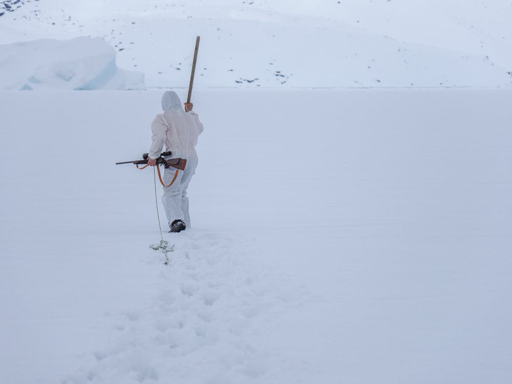 Seal hunter walking on the sea ice with his riffle