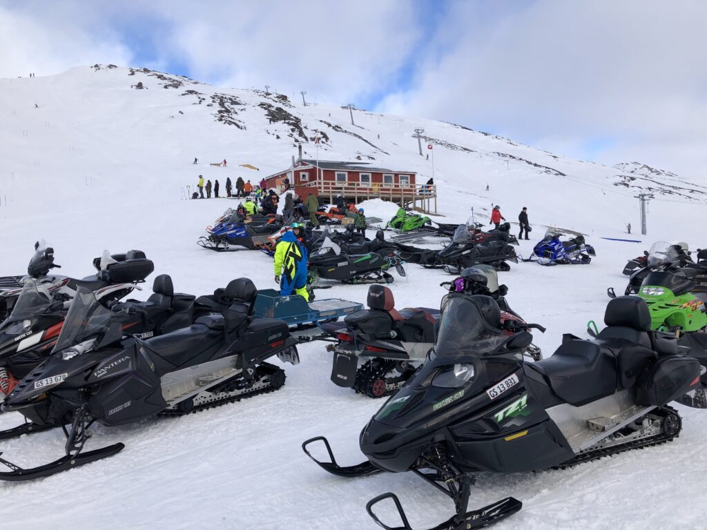 Snowmobiles and a red cabin