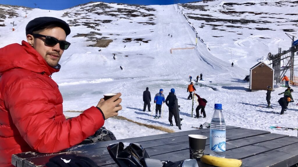 Man enjoying a cup of coffee at the ski slope