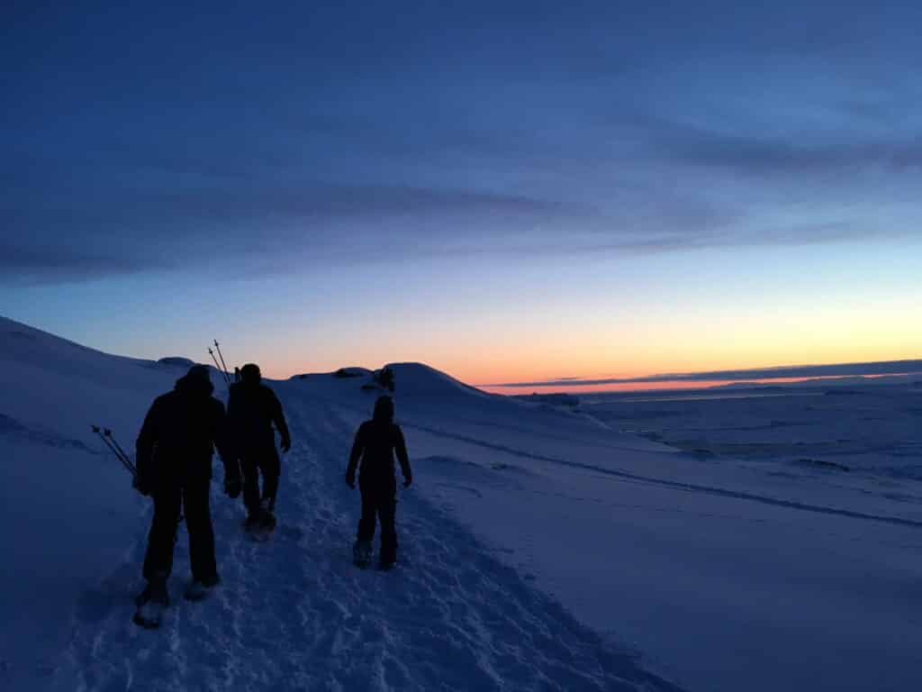 People snowshoeing under a red sky