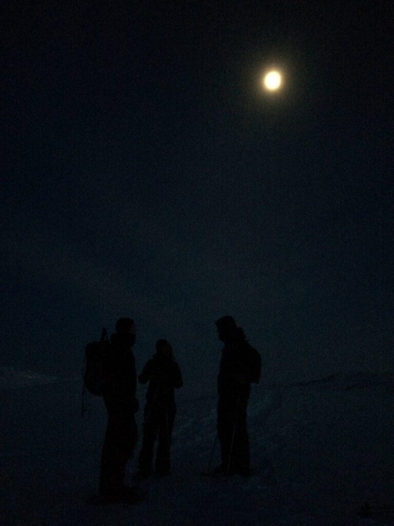 People standing in the dark under the moon