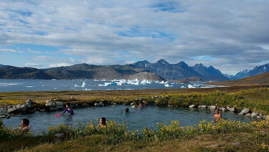 People bathing in hot spring with icebergs floating by in the fjord