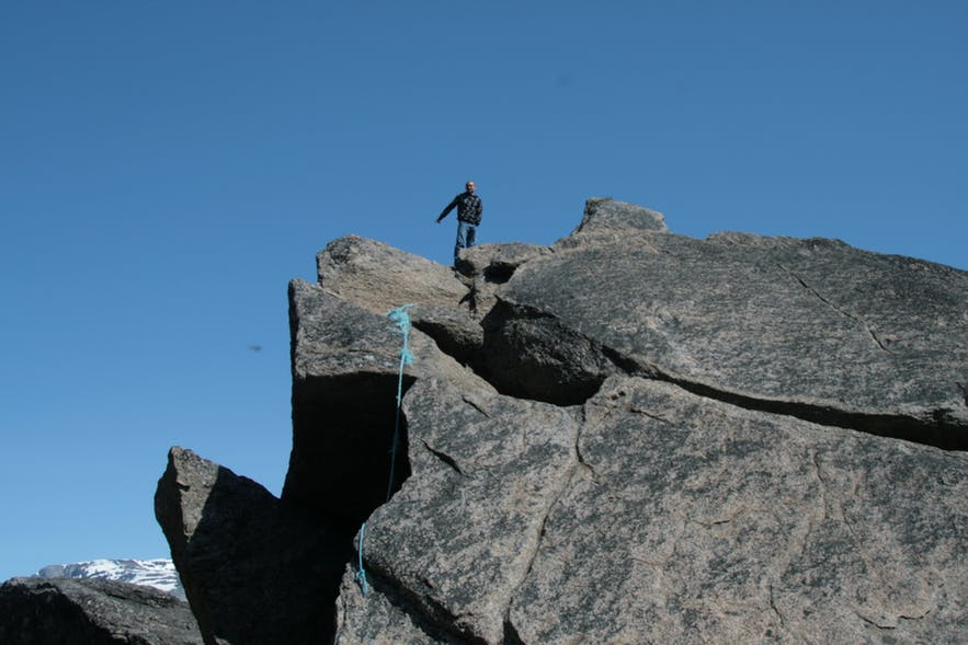 Man on top of a large rock in the south of Greenland