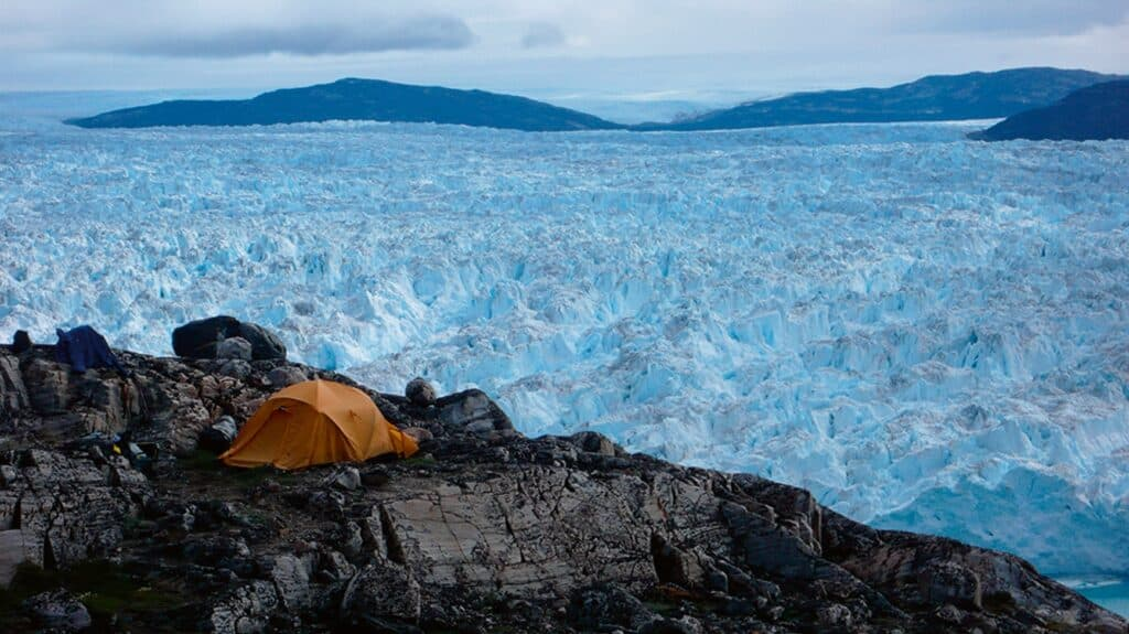 An orange tent next to a large glacier in Greenland