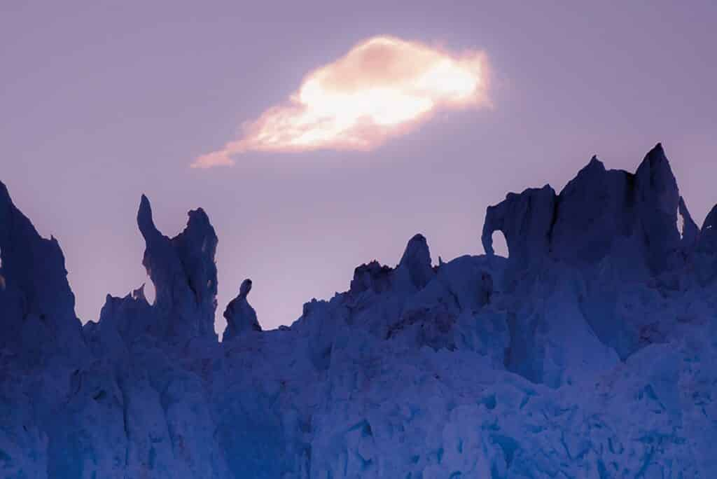 Cloud blocking the sun thus creating a purple looking sky over a glacier in Greenland