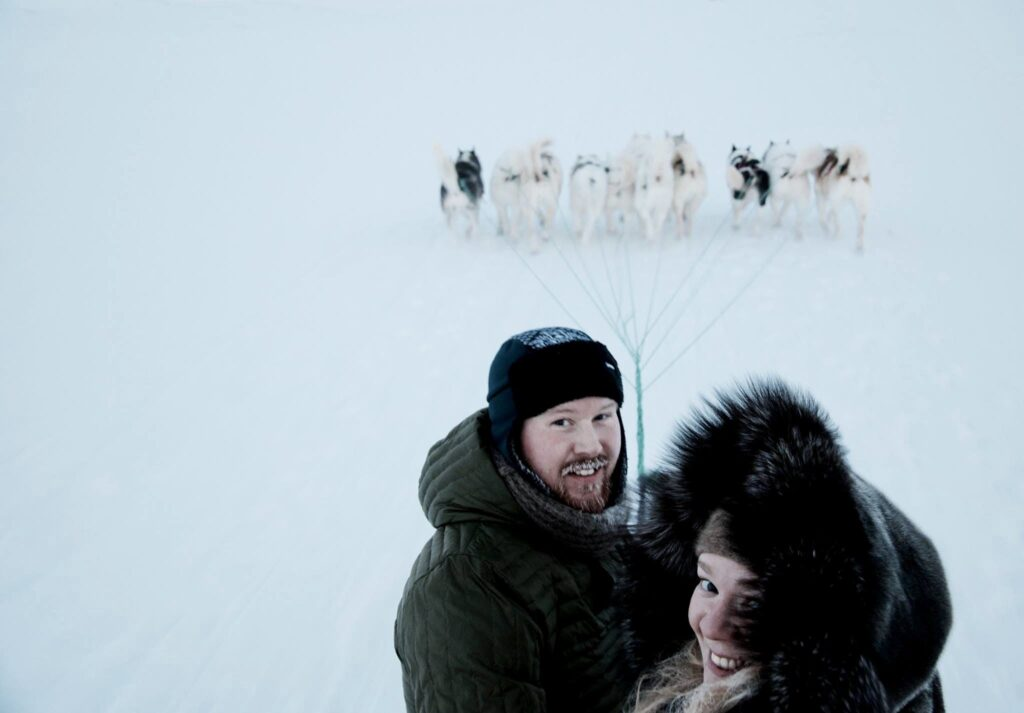 Couple standing in front of a pack of sled dogs