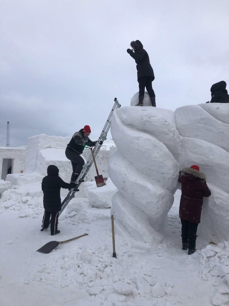 People working on a snow sculpture
