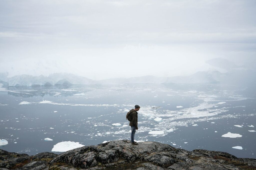 Man at the top of a mountian with icebergs in the back
