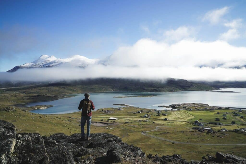 Man looking over the fjord and mountians