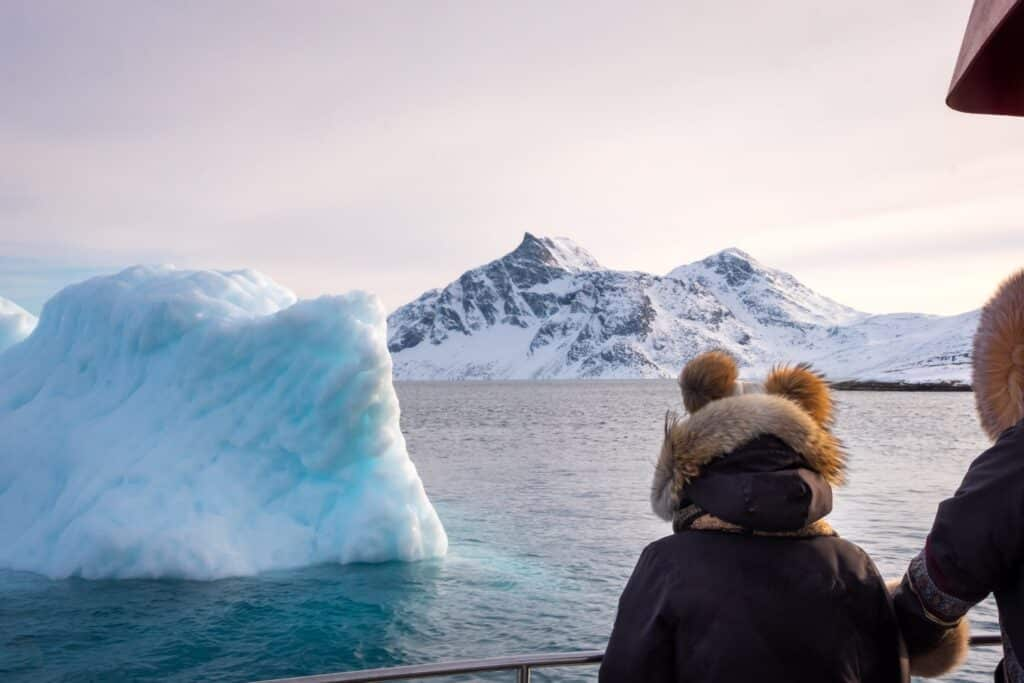 People looking at an iceberg on a boat tour of the Nuuk Fjord in Winter - Guide to Greenland