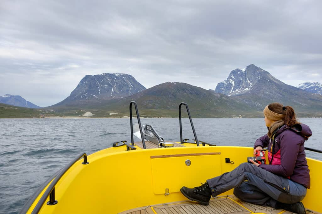 Person sitting in the front of a boat on a tour to Qooqqut with the settlement in the distance - summer - Guide to Greenland