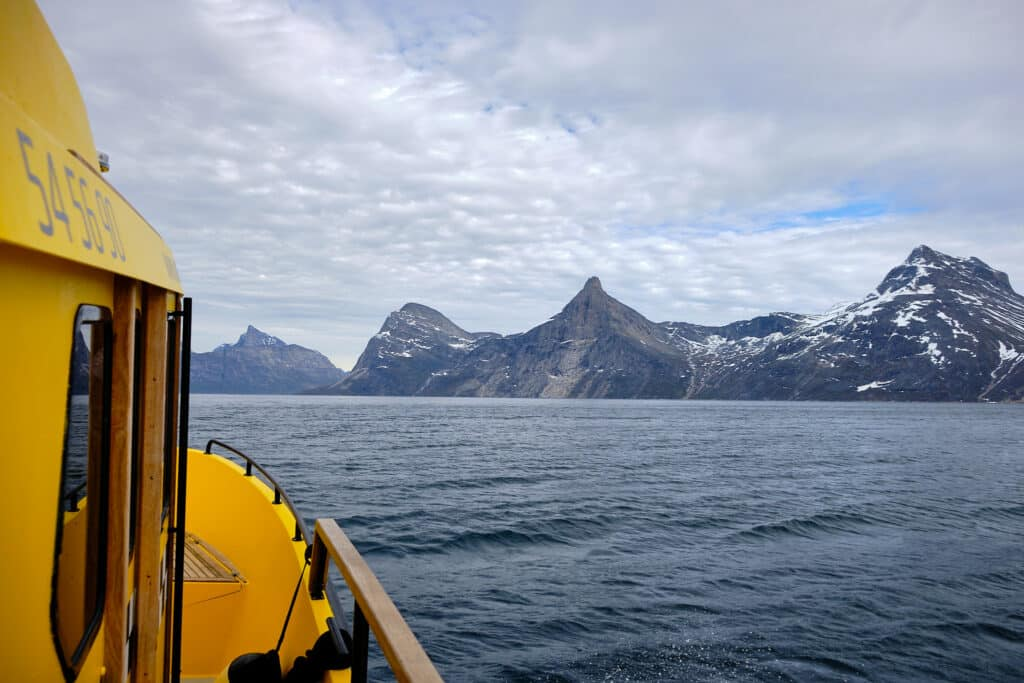 boat tour on the nuuk fjord heading towards qooqqut on a cloudy day - summer - guide to greenland