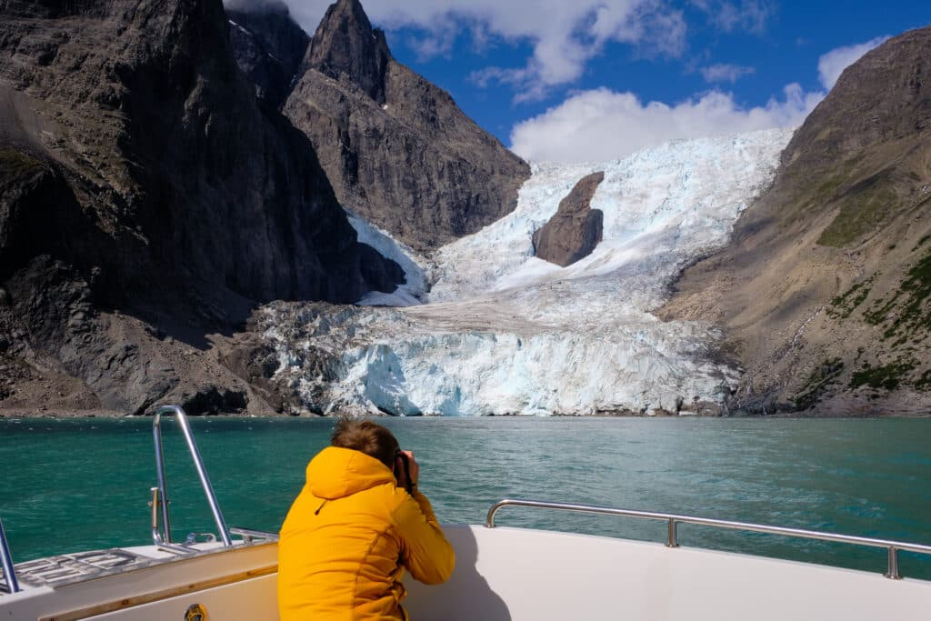 Photographer taking pictures of one of the many glaciers in the Eternity Fjord north of Maniitsoq - Guide to Greenland