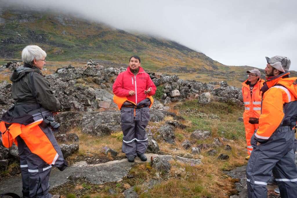 Guide explaining some of the other ruins at the Hvalsey Church site - Qaqortoq