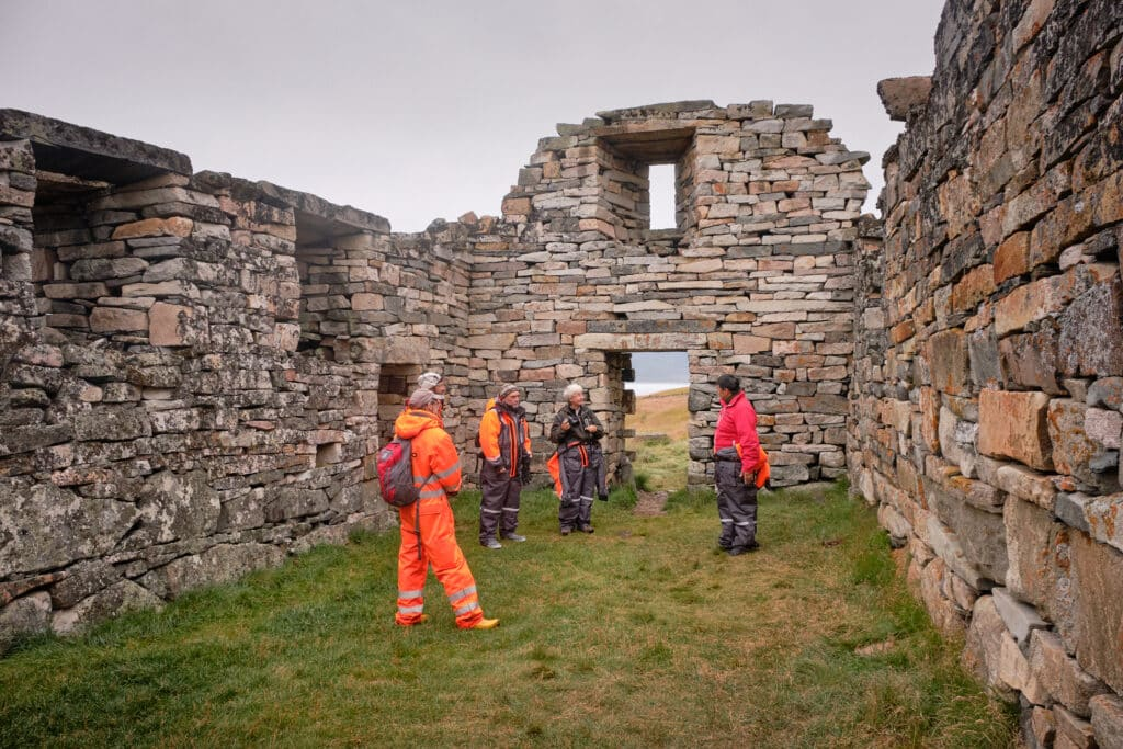 Learning about the Hvalsey Church on a tour - Qaqortoq