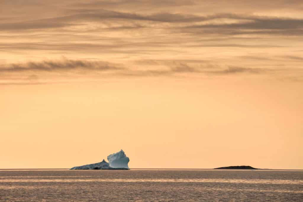 Enormous icebergs against a sunset near Aasiaat