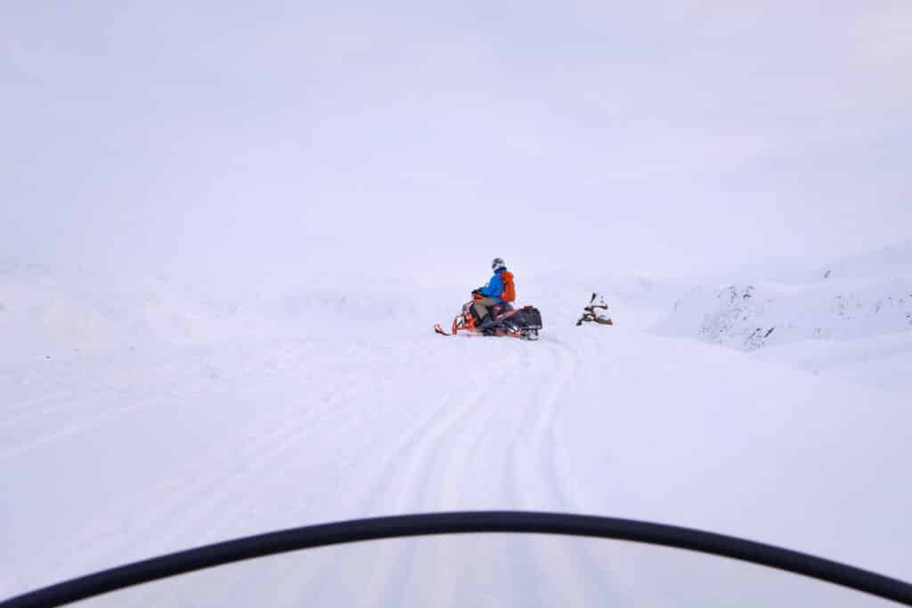 View from the drivers seat of a snowmobile near Sisimiut