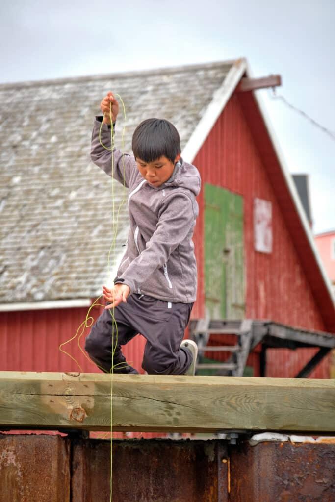 Kids fishing from the dock at Akunnaaq near Aasiaat