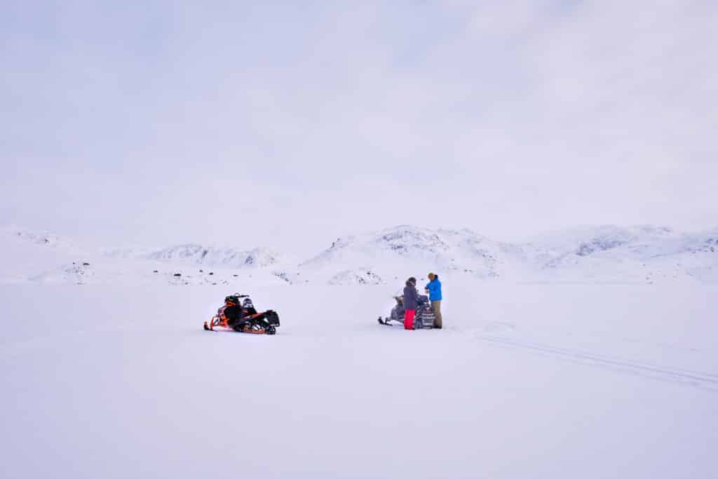 People having a Picnic lunch in the middle of the frozen Kangerlusarsuk Tulleq fjord near sisimiut on a snowmobile excursion