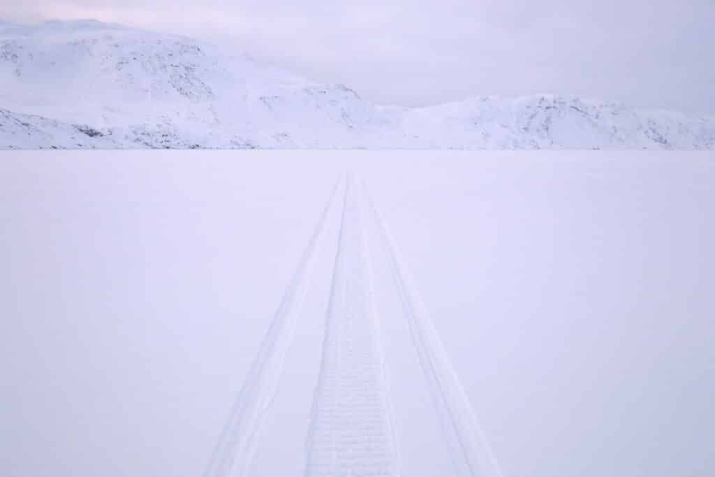 Snowmobile tracks across the frozen Kangerlusarsuk Tulleq fjord near Sisimiut
