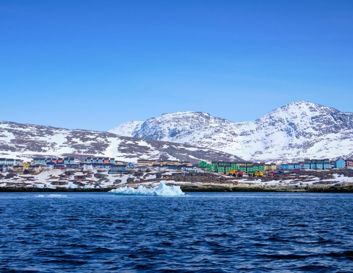 Colorful houses of Nuuk with Lille and Store Malene in the background as seen from a boat tour with Guide to Greenland