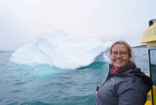 Girl-smiling-with-iceberg-in-background-Guide-to-Greenland