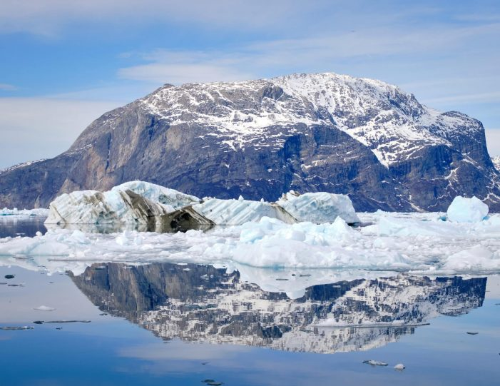Mountain at the entrance to the Nuuk Icefjord and icebergs reflected in the water on a boat tour with Guide to Greenland