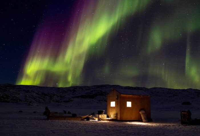 Northern-lights-over-an-illuminated-hunting-cabin-near-Ikerasak-close-to-Uummanaq-Guide-to-Greenland