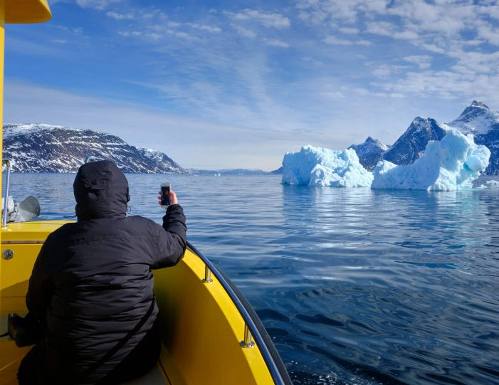 Passenger taking a photo of a large iceberg on a boat tour to the Nuuk Icefjord with Guide to Greenland