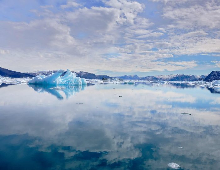 Sky and iceberg reflected in the water the Nuuk Icefjord on a boat tour with Guide to Greenland