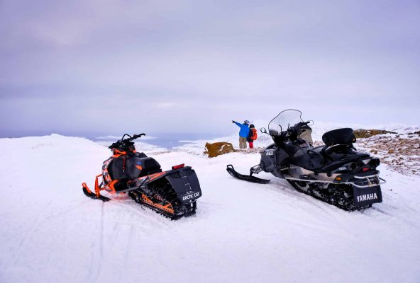 Snowmobilers and their machines at the viewpoint over Sisimiut