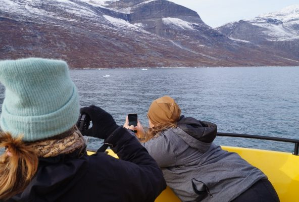 Two-women-taking-pictures-of-whale-from-boat-Guide-to-Greenoland