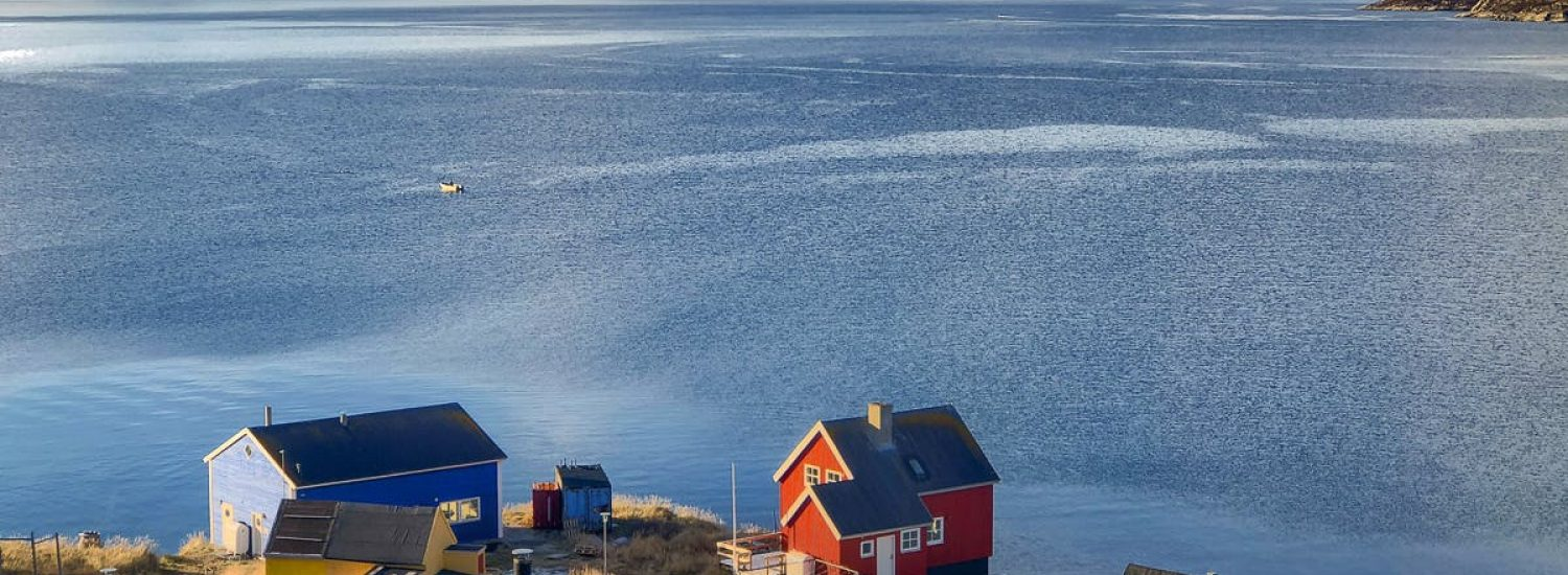 View over the colorful houses of Kapisillit looking out into the fjord - summer - Guide to Greenland