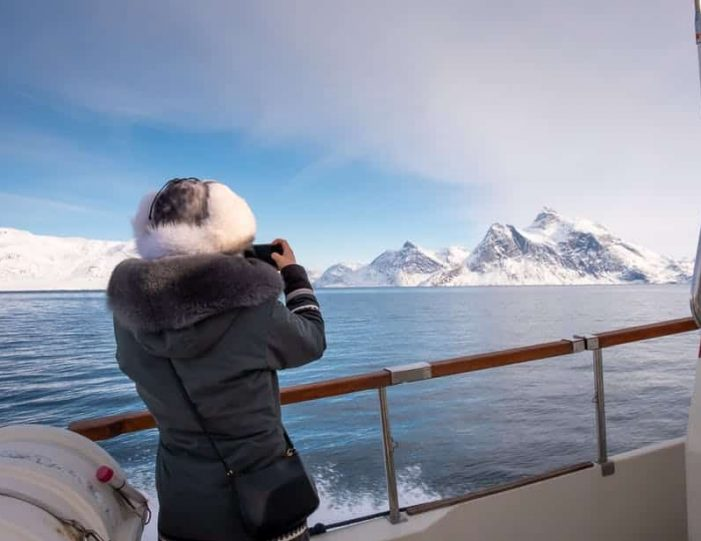 client-taking-photographs-of-sermitsiaq-mountain-from-a-boat-tour-in-nuuk-fjord - Guide to Greenland