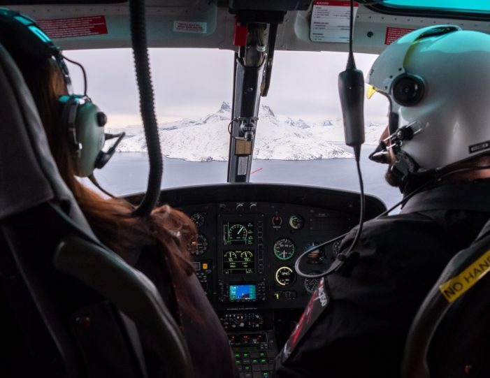 looking-through-the-helicopter-windscreen-at-sermitsiaq-with-pilot-and-passenger-in-the-foreground-helicopter-summit-scenic-flight-nuuk -winter- Guide to Greenland