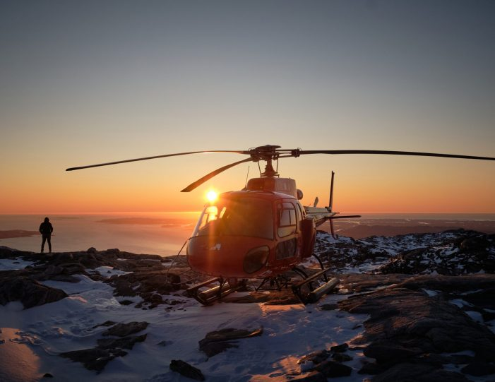 nuuk-scenic-helicopter-summit-flight-at-sunset-helicopter-and-silhouetted-person-summer-Guide-to-Greenland