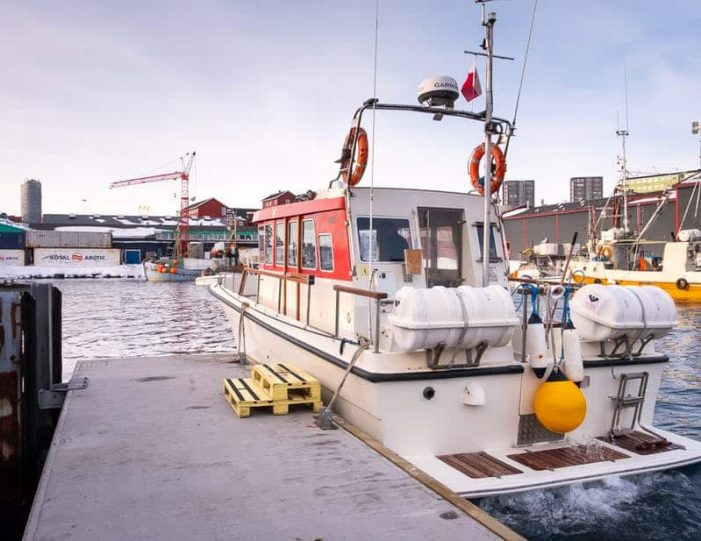 one-of-the-closed-boats-used-for-nuuk-fjord-tours-at-dock-in-the-industrial-harbour-of-nuuk - Guide to Greenland