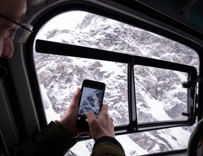 passenger-taking-a-photograph-while-passing-side-of-a-mountain-on-the-helicopter-summit-scenic-flight-nuuk - winter - Guide to Greenland