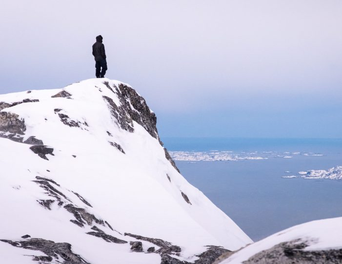 person-standing-on-a-ledge-overlooking-nuuk-fjord-from-on-high-helicopter-summit-scenic-flight-nuuk -winter- Guide to Greenland