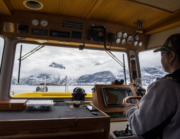sailing-in-nuuk-fjord-during-cloudy-day-captain-and-a-view-from-the-cabin-summer-guide-to-greenland-5